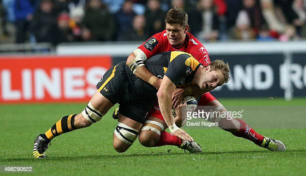 Joe Launchbury of Wasps is tackled by Juan Smith during the European Rugby Champions Cup match between Wasps and Toulon at the Ricoh Arena on...