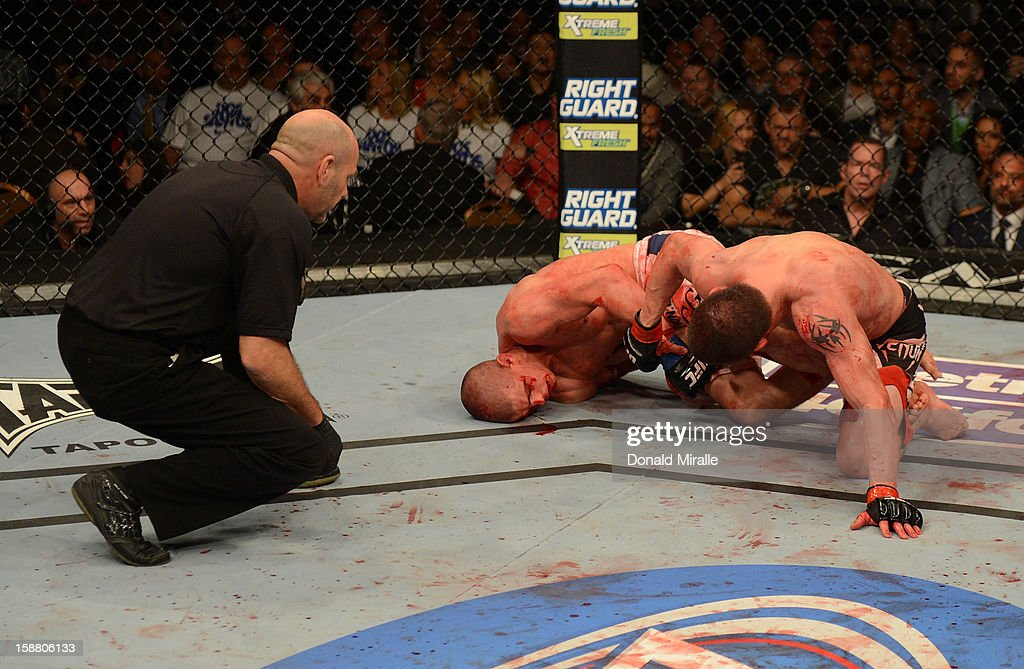 Joe Lauzon (center) attempts to submit Jim Miller (right) as referee Yves Lavigne looks on during their lightweight fight at UFC 155 on December 29, 2012 at MGM Grand Garden Arena in Las Vegas, Nevada.