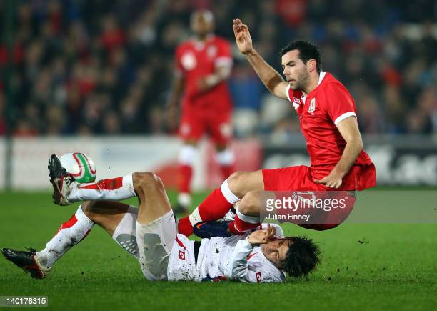 Joe Ledley of Wales lands on Jose Salvatierra of Costa Rica during the Gary Speed Memorial International Match between Wales and Costa Rica at the...
