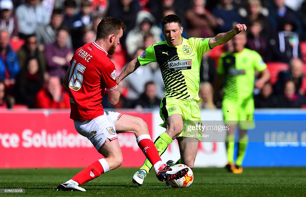 Joe Lolley of Huddersfield Town is tackled by Alex Pearce of Bristol City during the Sky Bet Championship match between Bristol City and Huddersfield Town at Ashton Gate on April 30, 2016 in Bristol, England.