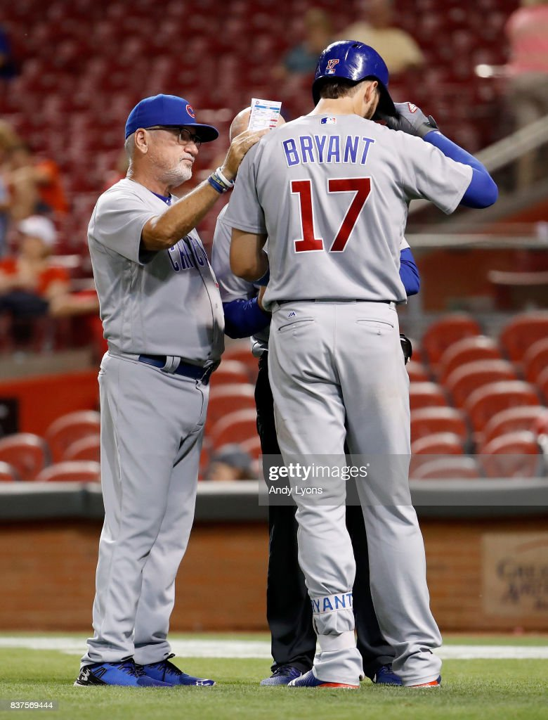 Joe Maddon the manager of the Chicago Cubs checks on Kris Bryant #17 after Bryant was hit by a pitch in the 9th inning against the Cincinnati Reds at Great American Ball Park on August 22, 2017 in Cincinnati, Ohio.