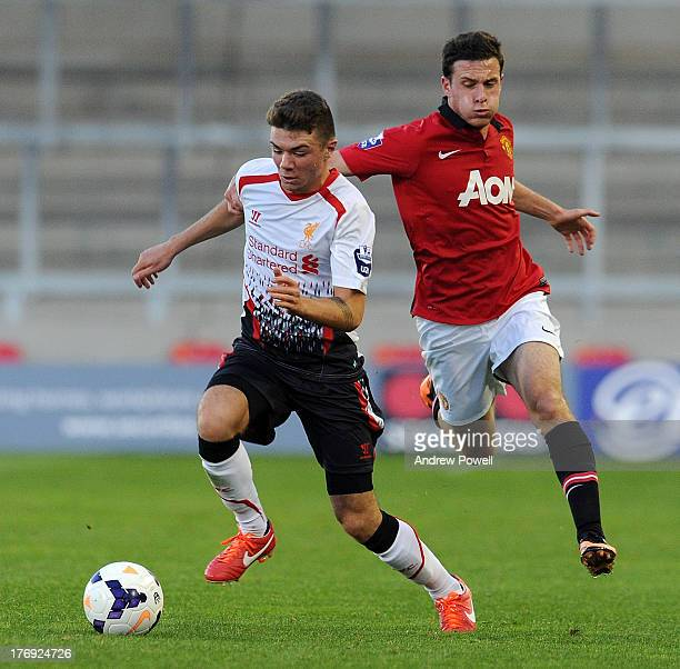 Joe Maguire of Liverpool competes with Angelo Henriquez of Manchester United during the Barclays U21s Premier League match between Manchester United...