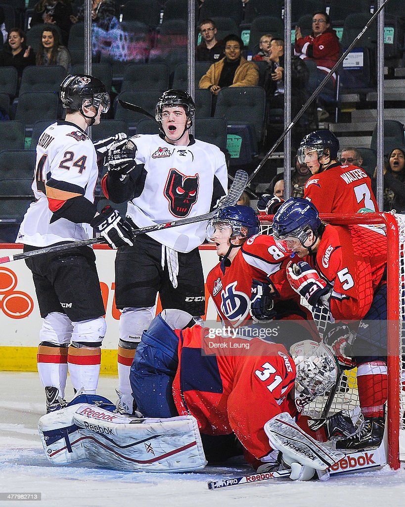Joe Mahon #24 (L) and Linden Penner #22 of the Calgary Hitmen celebrate a goal against the Lethbridge Hurricanes during a WHL game at Scotiabank Saddledome on March 11, 2014 in Calgary, Alberta, Canada.