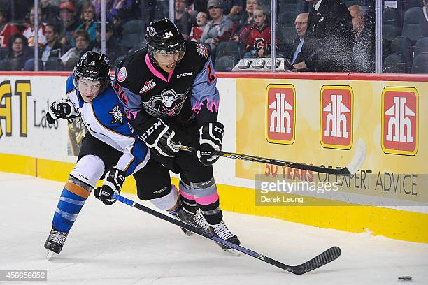 Joe Mahon of the Calgary Hitmen battles for the puck against Cale Fleury of the Kootenay Ice during a WHL game at Scotiabank Saddledome on October 4...
