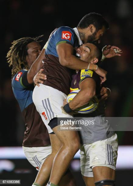 Joe Marchant of Harlequins celebrates scoring a try with Alofa Alofa and Marland Yarde during the Aviva Premiership match between Harlequins and...