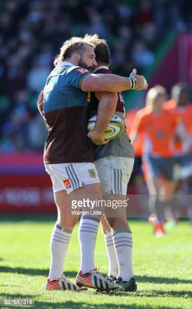 Joe Marler of Harlequins congratulates team mate Rob Buchanan after scoring the opening try during the Aviva Premiership match between Harlequins and...