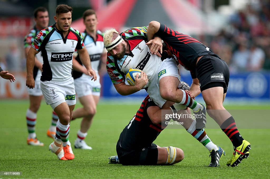 Joe Marler of Harlequins is tackled during the Aviva Premiership Semi Final match between Saracens and Harlequins at Allianz Park on May 17, 2014 in Barnet, England.