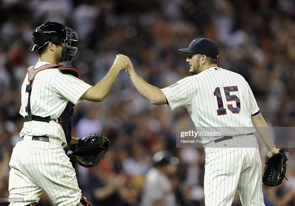 Joe Mauer #7 and Glen Perkins #15 of the Minnesota Twins celebrate a win of the game against the Houston Astros on August 3, 2013 at Target Field in Minneapolis, Minnesota. The Twins defeated the Astros 6-4.
