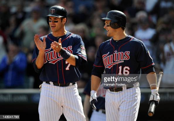 Joe Mauer and Josh Willingham of the Minnesota Twins celebrate a home run by Justin Morneau during the game against the Los Angeles Angels of Anaheim...