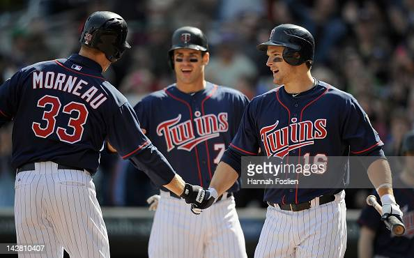 Joe Mauer and Josh Willingham of the Minnesota Twins congratulate Justin Morneau of the Minnesota Twins on a two run home run against the Los Angeles...