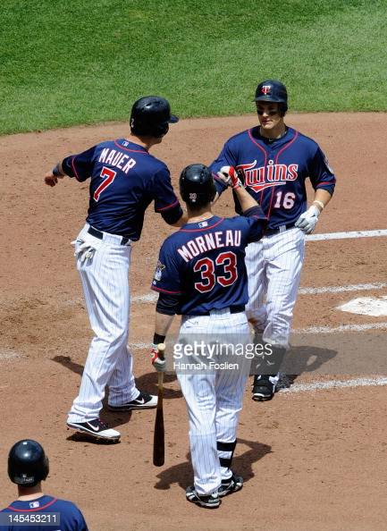 Joe Mauer and Justin Morneau of the Minnesota Twins congratulate Josh Willingham on a two run home run during the fourth inning against the Oakland...