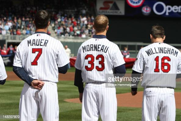 Joe Mauer Justin Morneau and Josh Willingham of the Minnesota Twins stand during the national anthem prior to the game against the Los Angeles Angels...