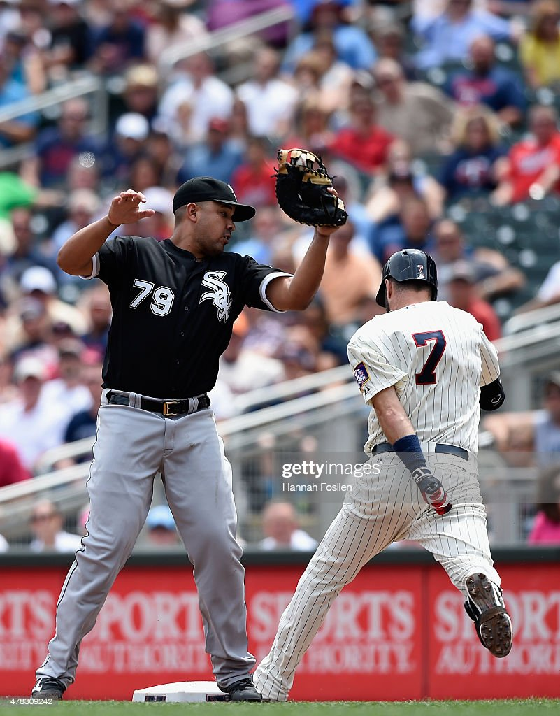 Joe Mauer of the Minnesota Twins beats out a tag from Jose Abreu of the Chicago White Sox at first base during the sixth inning of the game on June...