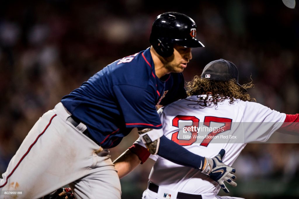 Joe Mauer #7 of the Minnesota Twins collides with Heath Hembree #37 of the Boston Red Sox during the eighth inning of a game on June 28, 2017 at Fenway Park in Boston, Massachusetts.