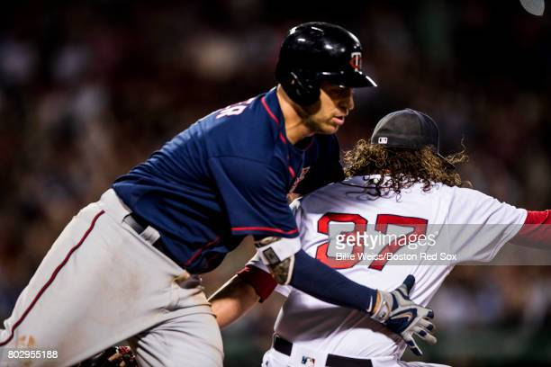 Joe Mauer of the Minnesota Twins collides with Heath Hembree of the Boston Red Sox during the eighth inning of a game on June 28 2017 at Fenway Park...