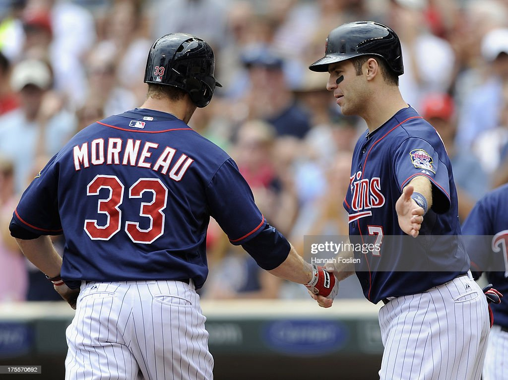Joe Mauer #7 of the Minnesota Twins congratulates teammate Justin Morneau #33 on hitting a two run home run against the Houston Astros during the first inning of the game on August 4, 2013 at Target Field in Minneapolis, Minnesota.