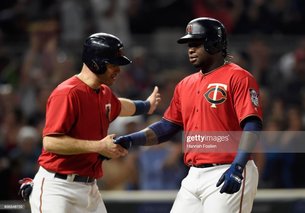 Joe Mauer #7 of the Minnesota Twins congratulates teammate Miguel Sano #22 on two-run home run against the Arizona Diamondbacks during the seventh inning of the game on August 18, 2017 at Target Field in Minneapolis, Minnesota. The Twins defeated the Diamondbacks 10-3.