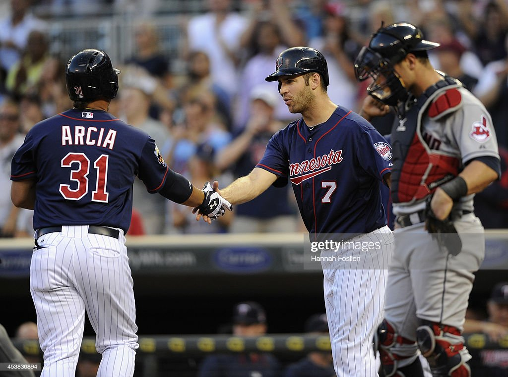 <a gi-track='captionPersonalityLinkClicked' href=/galleries/search?phrase=Joe+Mauer&family=editorial&specificpeople=214614 ng-click='$event.stopPropagation()'>Joe Mauer</a> #7 of the Minnesota Twins congratulates teammate <a gi-track='captionPersonalityLinkClicked' href=/galleries/search?phrase=Oswaldo+Arcia&family=editorial&specificpeople=8948415 ng-click='$event.stopPropagation()'>Oswaldo Arcia</a> #31 on a three-run home run as <a gi-track='captionPersonalityLinkClicked' href=/galleries/search?phrase=Yan+Gomes&family=editorial&specificpeople=9004037 ng-click='$event.stopPropagation()'>Yan Gomes</a> #10 of the Cleveland Indians looks on during the first inning of the game on August 19, 2014 at Target Field in Minneapolis, Minnesota.