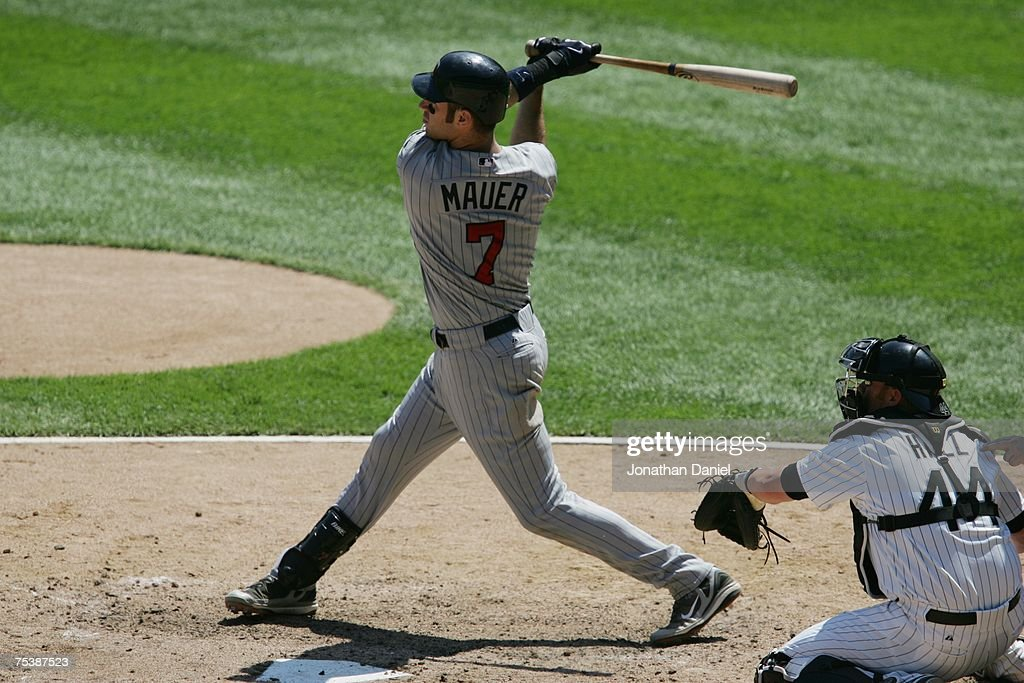 Joe Mauer of the Minnesota Twins gets a hit as catcher Toby Hall of the Chicago White Sox looks on during the MLB game on July 6 2007 at US Cellular...