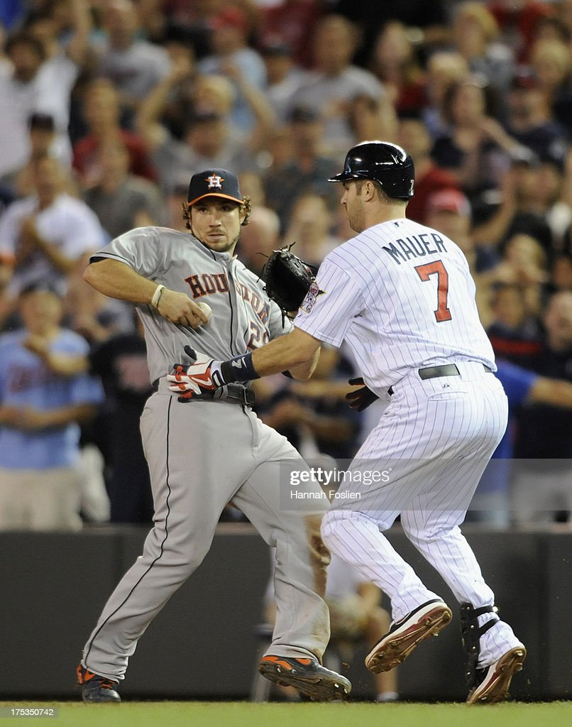 <a gi-track='captionPersonalityLinkClicked' href=/galleries/search?phrase=Joe+Mauer&family=editorial&specificpeople=214614 ng-click='$event.stopPropagation()'>Joe Mauer</a> #7 of the Minnesota Twins gets tangled up with <a gi-track='captionPersonalityLinkClicked' href=/galleries/search?phrase=Brett+Wallace&family=editorial&specificpeople=2364861 ng-click='$event.stopPropagation()'>Brett Wallace</a> #29 of the Houston Astros after reaching first base safely during the ninth inning of the game on August 2, 2013 at Target Field in Minneapolis, Minnesota. The Twins defeated the Astros 4-3 in thirteen inning.