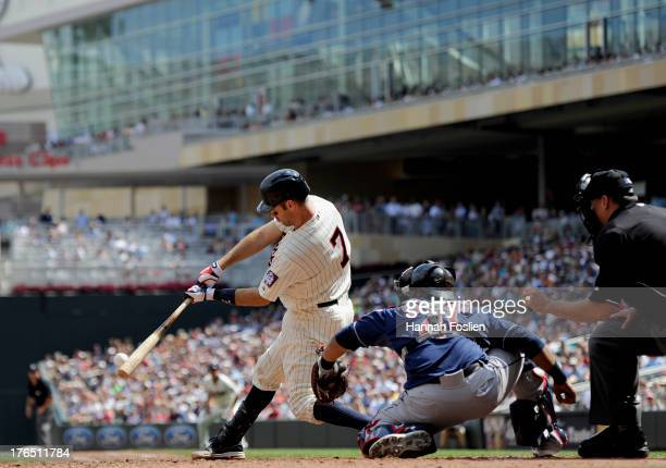Joe Mauer of the Minnesota Twins hits a two run single as Carlos Santana of the Cleveland Indians catches during the seventh inning of the game on...