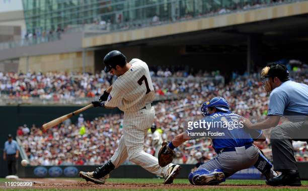 Joe Mauer of the Minnesota Twins hits an RBI single as Matt Treanor of the Kansas City Royals catches in the first inning on July 17 2011 at Target...