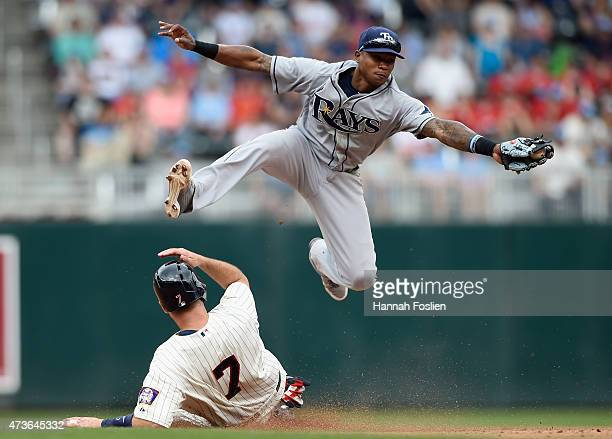 Joe Mauer of the Minnesota Twins is safe at second base as Tim Beckham of the Tampa Bay Rays fields the throw from teammate Kevin Jepsen during the...