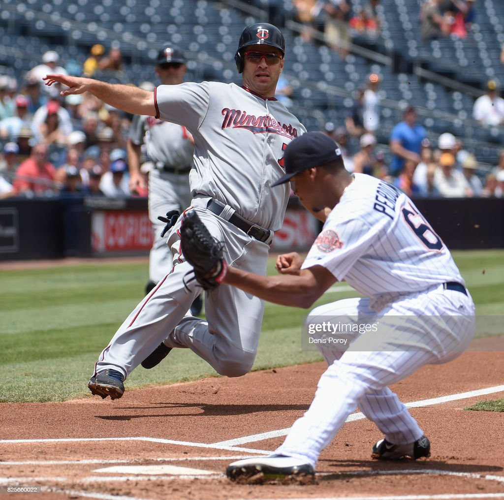 Joe Mauer #7 of the Minnesota Twins is tagged out at the plate by Luis Perdomo #61 of the San Diego Padres during the first inning of a baseball game at PETCO Park on August 2, 2017 in San Diego, California.