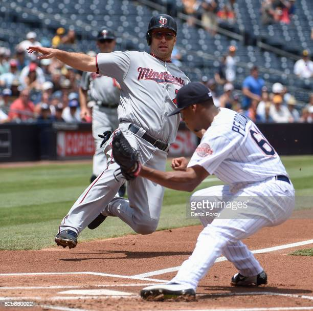 Joe Mauer of the Minnesota Twins is tagged out at the plate by Luis Perdomo of the San Diego Padres during the first inning of a baseball game at...