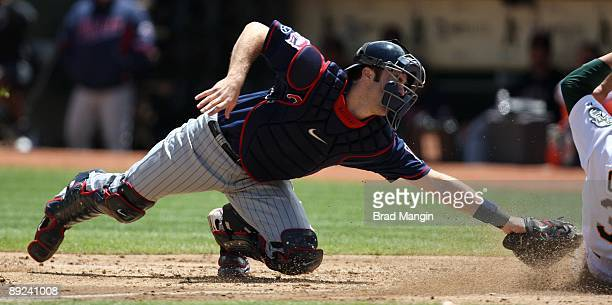 Joe Mauer of the Minnesota Twins makes a late tag as Oakland Athletics base runner Jack Cust slides home safely during the game at the OaklandAlameda...