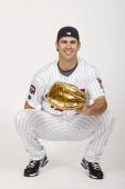 Joe Mauer of the Minnesota Twins poses with the 2008 Golden Glove Award he earned before the game against the Seattle Mariners on May 9 2009 at the...