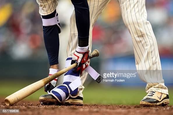 Joe Mauer of the Minnesota Twins removes his shin guard after walking against the Baltimore Orioles during the game on May 11 2016 at Target Field in...