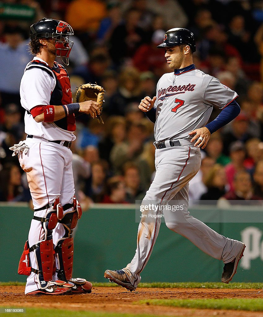 Joe Mauer #7 of the Minnesota Twins scores on a sacrifice fly by Justin Morneau #33 of the Minnesota Twins in the 5th inning as Jarrod Saltalamacchia #39 of the Boston Red Sox looks away at Fenway Park on May 6, 2013 in Boston, Massachusetts.
