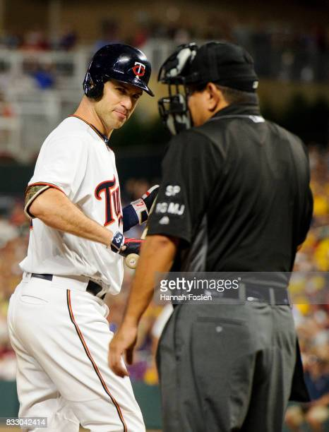 Joe Mauer of the Minnesota Twins speaks to home plate umpire Alfonso Marquez after striking out against the Cleveland Indians during the game on...