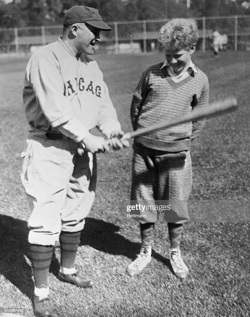 Joe McCarthy, manager of the Chicago Cubs, shows Bill Veeck the proper technique for holding a baseball bat during the Cubs' spring training.