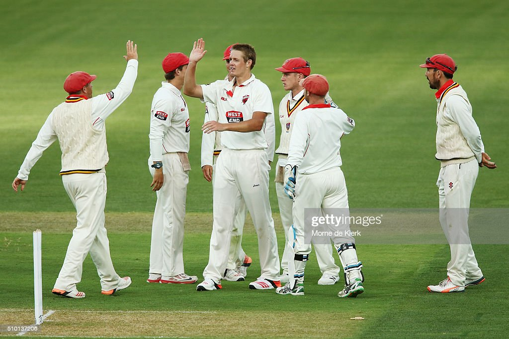 Joe Mennie of the Redbacks celebrates with teammates after he got the wicket of Glenn Maxwell of the VIC Bushrangers during day one of the Sheffield Shield match between South Australia and Victoria at Adelaide Oval on February 14, 2016 in Adelaide, Australia.