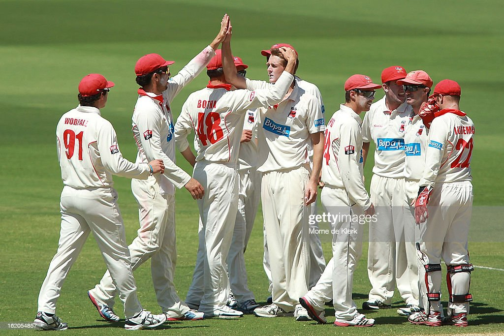 Joe Mennie (C) of the Redbacksis congratulated by team mates after getting a wicket during day one of the Sheffield Shield match between the South Australian Redbacks and the New South Wales Blues at Adelaide Oval on February 19, 2013 in Adelaide, Australia.