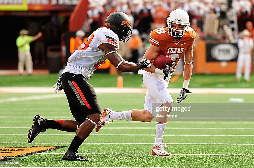 Joe Mitchel #29 of the Oklahoma State Cowboys pursues Jaxon Shipley #8 of the Texas Longhorns during a game at Darrell K Royal-Texas Memorial Stadium on November 16, 2013 in Austin, Texas. Oklahoma State won the game 38-13.