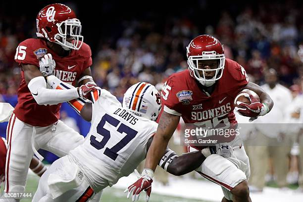 Joe Mixon of the Oklahoma Sooners is tackled by Carl Lawson of the Auburn Tigers during the Allstate Sugar Bowl at the MercedesBenz Superdome on...