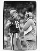 Joe Montana and head coach Bill Walsh of the San Francisco 49ers discuss strategy during the game against the Los Angeles Raiders at Candlestick Park...