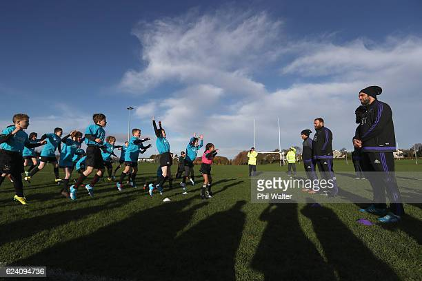 Joe Moody Aaron Smith Charlie Faumuina and Sam Whitelock of the New Zealand All Blacks are welcomed with a haka during a skills clinic with children...