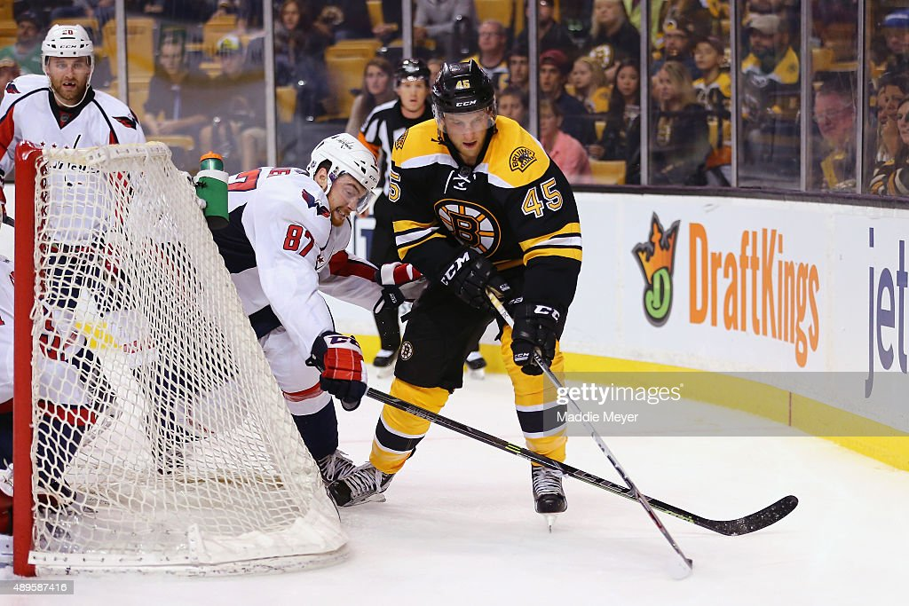 Joe Morrow of the Boston Bruins and Liam O'Brien of the Washington Capitals battle for control of the puck during the third period at TD Garden on...