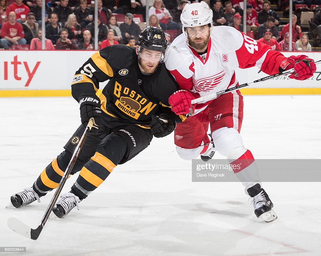 Joe Morrow #45 of the Boston Bruins battles for position with Henrik Zetterberg #40 of the Detroit Red Wings during an NHL game at Joe Louis Arena on January 18, 2017 in Detroit, Michigan.