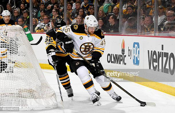 Joe Morrow of the Boston Bruins handles the puck against Carl Hagelin of the Pittsburgh Penguins at PPG Paints Arena on January 22 2017 in Pittsburgh...