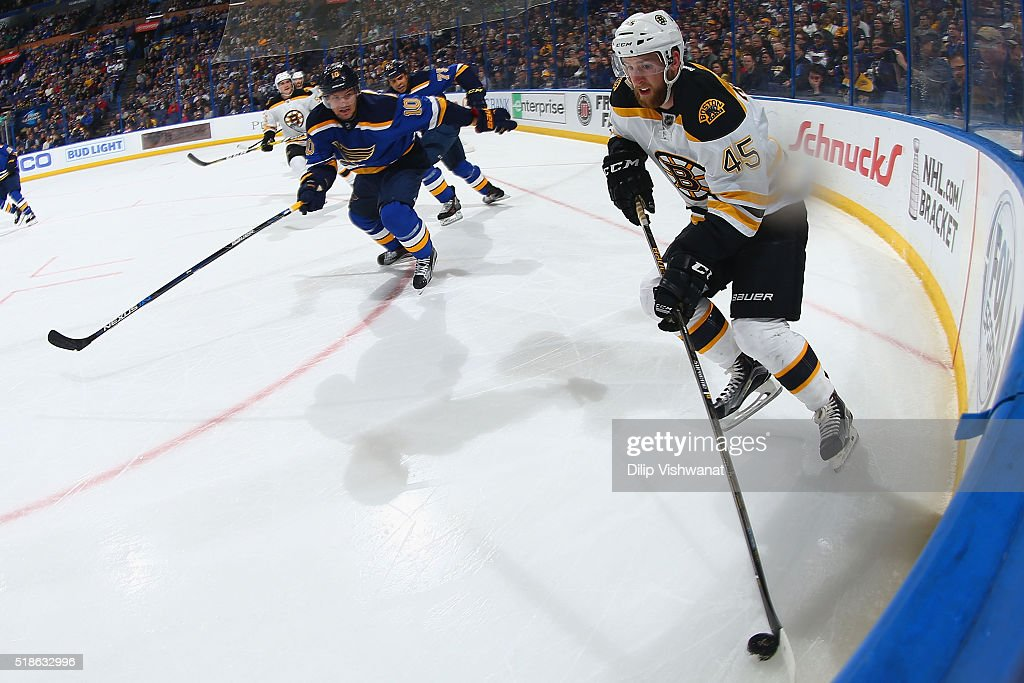 Joe Morrow of the Boston Bruins looks to clear the puck against Scottie Upshall of the St Louis Blues at the Scottrade Center on April 1 2016 in St...
