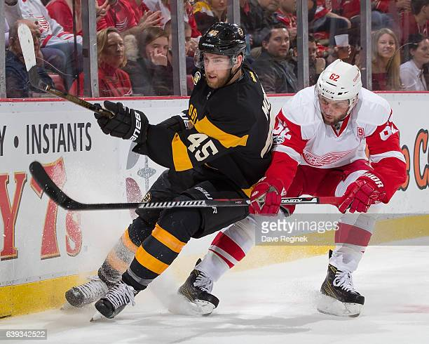 Joe Morrow of the Boston Bruins passes the puck in front of Thomas Vanek of the Detroit Red Wings during an NHL game at Joe Louis Arena on January 18...