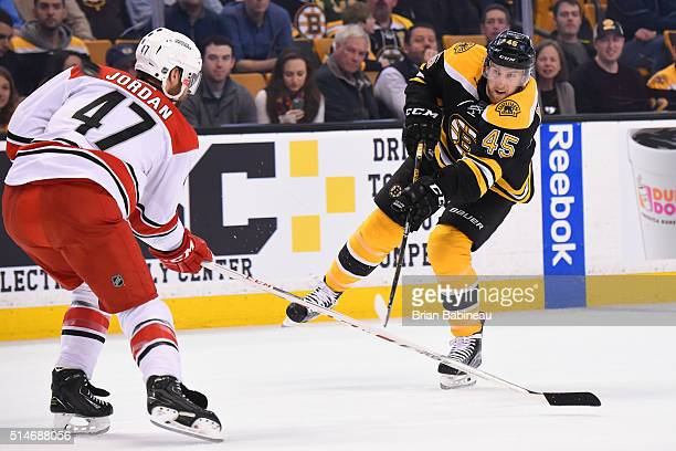 Joe Morrow of the Boston Bruins shoots the puck against Michal Jordan of the Carolina Hurricanes at the TD Garden on March 10 2016 in Boston...