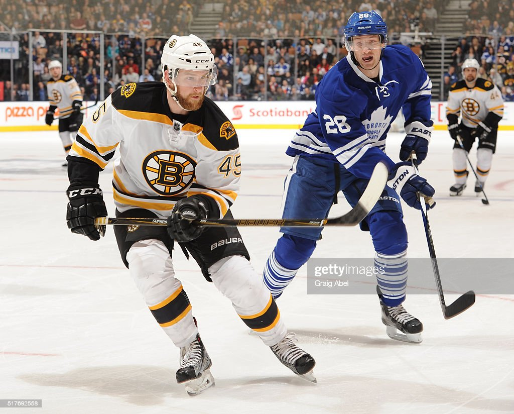 Joe Morrow of the Boston Bruins skates against Brad Boyes of the Toronto Maple Leafs during game action on March 26 2016 at Air Canada Centre in...