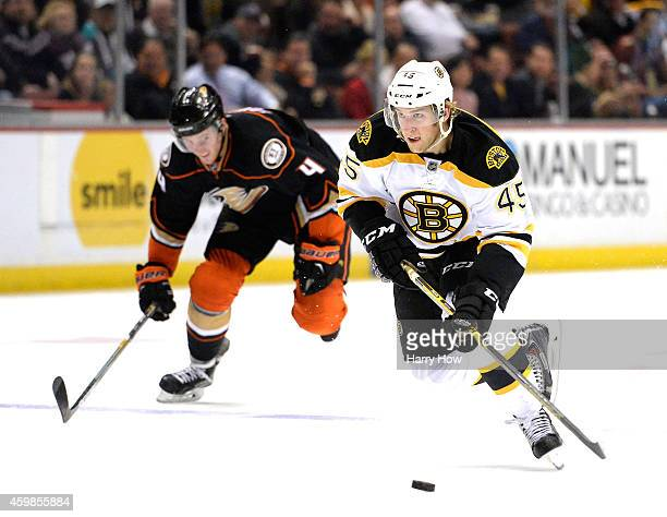 Joe Morrow of the Boston Bruins skates in on a breakaway in front of Cam Fowler of the Anaheim Ducks at Honda Center on December 1 2014 in Anaheim...