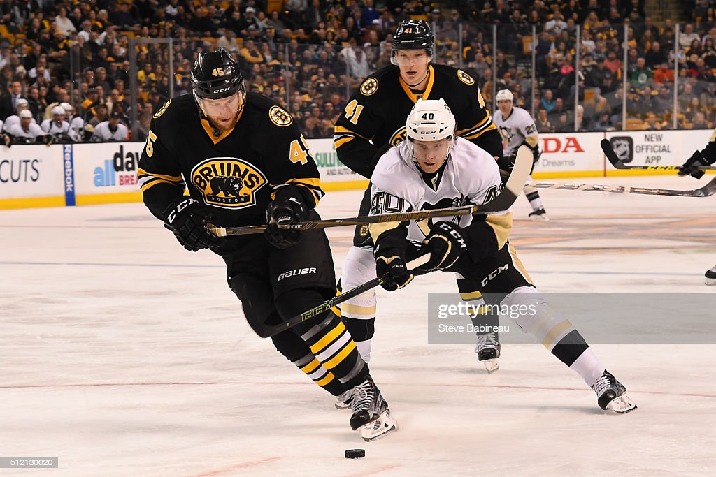 Joe Morrow of the Boston Bruins skates with the puck against Oskar Sundqvist of the Pittsburgh Penguins at the TD Garden on February 24 2016 in...